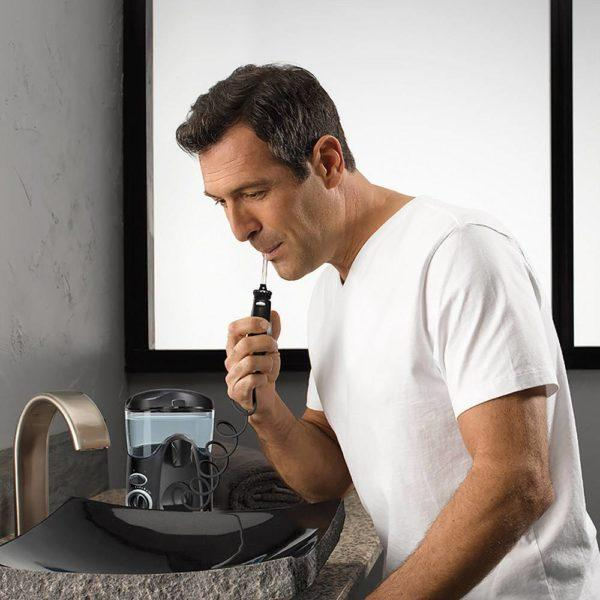 Man using the Waterpik WP-100 water flosser